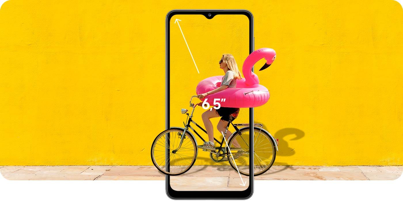 Kobieta na rowerze w dmuchanym flamingu, informacja o wielkości ekranu 6,5 cala