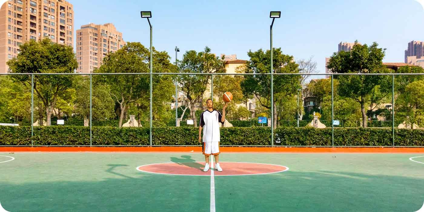 Ultraszerokokątny obiektyw, mężczyzna na środku boiska do koszykówki tle szeroki kadr